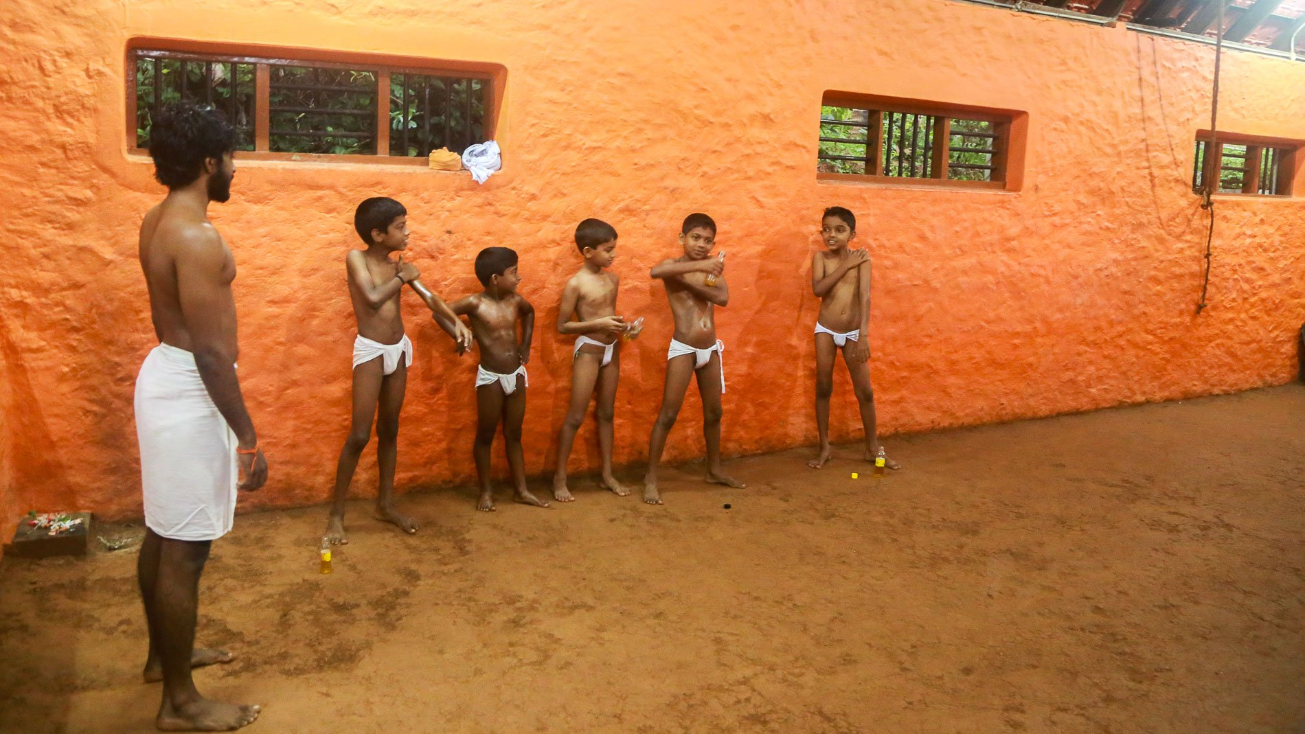 Local kids applying an oil before the kalaripayattu training. The Gurukkal - Sri Nath on the left side.